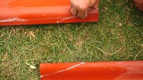 W górę męskiej pracownik ręki robi pomiarom na czerwony stalowy zadaszać outdoors klamerka Materiały i equipments dla obrazy stock