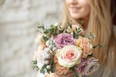W górę młodego caucasian kobiety mienia bukieta kwiaty, spojrzenia przez okno z szczęśliwym uśmiechem wewnątrz na twarzy pozycji zdjęcia royalty free