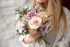 W górę młodego caucasian kobiety mienia bukieta kwiaty, spojrzenia przez okno z szczęśliwym uśmiechem wewnątrz na twarzy pozycji obraz royalty free
