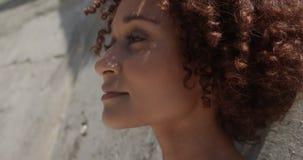 W górę młodej amerykanin afrykańskiego pochodzenia kobiety relaksuje na plaży w świetle słonecznym 4k zdjęcie wideo