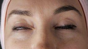 W górę młodej caucasian żeńskiej twarzy przed kosmetyczną procedurą Kobiet oczy zgodnie patrzeje w różnym zbiory