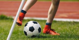 W górę Młodej gracz piłki nożnej kopania piłki na boisku do piłki nożnej Futbolowy Narożnikowy kopnięcie na smole obrazy royalty free