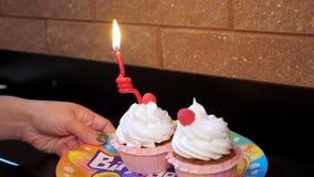 W górę, na świątecznym talerzu, dwa pięknych babeczkach z białą śmietanką i jagoda stojaku, Świeczka pali na jeden zbiory wideo