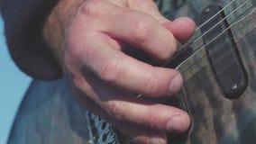 W górę palców bawić się na basowej gitarze zapas Gitarzysta bawić się basowej gitary sola outdoors w świetle dziennym Zakończenie zbiory wideo