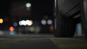 W górę pięknej szczupłej kobiety nogi w błękitnej szpilki kują dostawać w samochód przy nocą nad citylights bokeh tłem zbiory