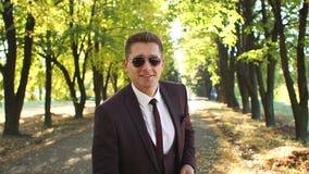 W górę pomyślnego biznesmena kładzenia na okularach przeciwsłonecznych w jesień parku zbiory