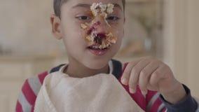 W górę portreta afroamerykańska chłopiec błocąca w torcie i ugniatać kawałek torta lying on the beach w talerzu na stole zdjęcie wideo