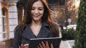 W górę portreta atrakcyjna młoda biznesowa kobieta używa pastylka komputer i uśmiecha się plenerowego, dziewczyna robi online zak zbiory wideo