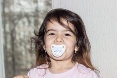 W g?r? portreta czteroletnia dziewczyna dziecko trzyma pacyfikator w jej usta zdjęcia stock