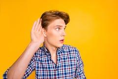 W górę portreta jego on przyglądający atrakcyjny skupiający się facet jest ubranym sprawdzać koszula próbuje słuchać poufnego zdjęcia stock