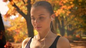 W górę portreta młoda caucasian dziewczyna, słuchający muzyka używać słuchawki i bieg zdjęcie wideo