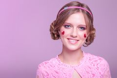 W górę portreta młoda pozytywna dziewczyna z fachowym codziennym makeup w różowych cieniach z obręczem i sercach z błyskotliwości zdjęcia stock