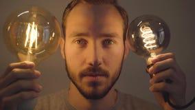 W górę portreta młody brodaty mężczyzna trzyma dwa żarówki i patrzeje kamerę Pojęcie światło i zmrok, pomysł zbiory wideo