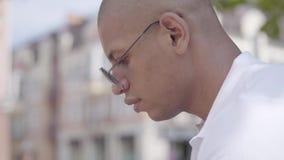W górę portreta rozważny przystojny łysy rozważny bliskowschodni mężczyzny obsiadanie przed budynkiem leisure zdjęcie wideo