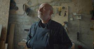 W górę portreta starsza męska ciesielka mistrza pozycja przy drewnianym manufaktury dopatrywaniem w kamerę jest poważny i zbiory