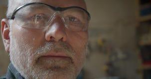 W górę portreta starszy cieśla w bezpieczeństwo maski dopatrywaniu w kamerę poważnie przy drewnianą manufakturą zbiory wideo