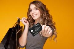W górę portreta szczęśliwa młoda brunetki kobiety mienia karta kredytowa i kolorowe torby na zakupy, patrzeje kamerę obraz royalty free