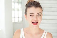 W górę portreta szczęśliwa młoda kobieta ono uśmiecha się i mruga Doskonalić skóra z piegami, falisty zdrowy włosy indoors przy obrazy stock