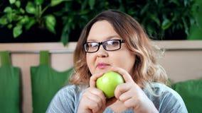 W górę portreta uśmiechnięta dieting gruba kobieta gryźć świeżą zieloną jabłczaną patrzeje kamerę zbiory wideo