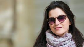 W górę portreta uśmiechnięta piękna młoda kobieta patrzeje kamerę w okularach przeciwsłonecznych zdjęcie wideo