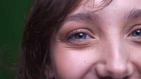 W górę przyrodniego twarz portreta młodej brunetki żeński uczeń ogląda smilingly w kamerę na zielonym tle zbiory