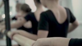 W górę ręk Małe baleriny ubierał w czarnych kostiumach W górę ręk trzyma baletniczego barre zdjęcie wideo