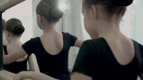 W górę ręk Małe baleriny ubierał w czarnych kostiumach W górę ręk trzyma baletniczego barre zbiory wideo