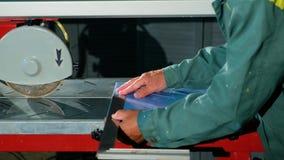 W górę ręk pracownik robi miarze z pomocy władcy płytką która kłama na dachówkowej tnącej maszynie zbiory