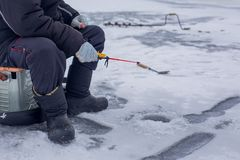 W górę ręki rybak chwyty łowią na zima połowu prąciu na zamarzniętej rzece z dziurą obrazy royalty free