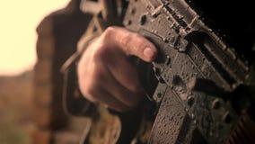 W górę ręki trzyma automatycznego pistolet, żołnierz, jest ubranym kamuflaż plenerowego podczas gdy raindrops spadają ciężko na o zbiory wideo