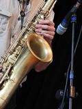 W górę saksofonisty bawić się jego instrument, obok mikrofonu obrazy royalty free