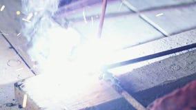W górę, spawacz spawa dwa metal części Robociarz w coveralls pracuje indoors zbiory