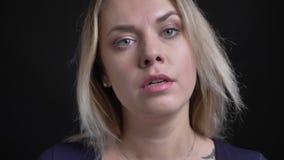 W górę strzału w średnim wieku blondynka bizneswoman w błękitnej bluzce z miarki neckline pozuje poważnie w kamerę przy zbiory
