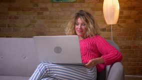 W górę strzału gospodyni domowa w różowym pulowerze ma wideo wzywa laptop i skinąć ono zgadzać się w domowej atmosferze zbiory