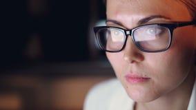 W górę strzału jest ubranym szkła piękna młoda kobieta używać komputerowy pracującego póżno przy nocą w ciemnym biurowym pokoju zbiory