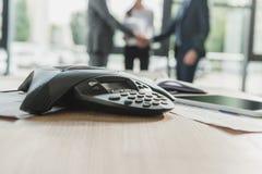 w górę strzału konferencyjny telefon z zamazanymi ludzie biznesu trząść ręki na tle zdjęcie royalty free