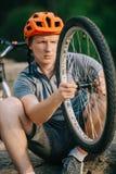 w górę strzału młody próbny rowerzysta egzamininuje rower zdjęcie stock