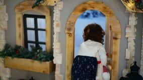 W górę strzału przy studiiem Mała dziewczynka otwiera drzwi spojrzenie wśrodku i drzwi zbiory