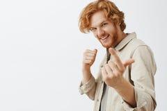 W górę strzału ufny figlarnie, szczęśliwy lekkomyślnie rudzielec mężczyzna z zaprasza z palcem wskazującym i obraz stock