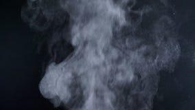 W górę strzału wielki vapouring dym z kiściami lata na czarnym tle zbiory