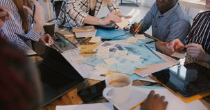 W górę strzału wieloetniczny drużynowy działanie wpólnie za stołowy pełnym notatki na brainstorming sesji w nowożytnym b zdjęcie wideo