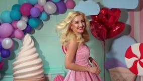 W górę szczęśliwej młodej dziewczyny w różowym smokingowym przędzalnictwie przy przyjęciem swobodny ruch zbiory wideo