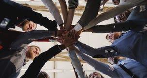 W górę szczęśliwej różnorodnej drużyny ludzie biznesu stawiać ręk wpólnie, klascze sukces i świętuje pod confetti przy biurem zbiory wideo