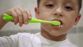 W górę twarzy chłopiec która trzyma toothbrush i szczotkuje jego zęby troszkę Mamy ręka stawia białą pastę do zębów dalej zbiory wideo