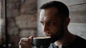 W górę walecznego mężczyzny pije kawę w kawiarni z szczecina i tatuować rękami zbiory