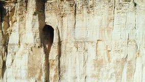 W górę widoku reliefowy biały faleza skłon z wielką dziurą lub grota po środku skłonu strza? Tajemnicza jama w zbiory