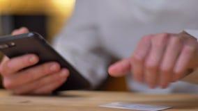 W górę wizerunku żeńskie ręki wykonuje bankowość transakcje używać kartę kredytową i smartphone zbiory wideo
