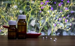 W górę wizerunku homeopatyczne pigułki w czerwonej łyżce i butelkach ciekła substancja z niektóre rozrzuconymi globula na drewnie fotografia royalty free