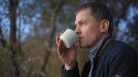 w górę, Zadumany mężczyzna Pije herbaty w jesień lesie zbiory