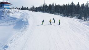 W g?r? narciarskiego sk?onu i ludzi narciarstwa i jazdy na snowboardzie puszek szlakowy pobliski iglasty las w zimie footage nart zdjęcie royalty free